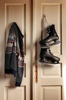 Anordnung mit den schlittschuhen und strickjacke, die an der tür hängen