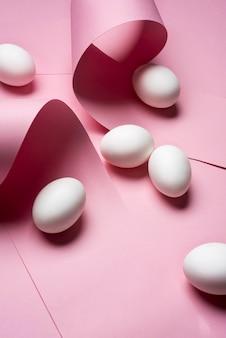 Anordnung mit eiern auf rosa hintergrund