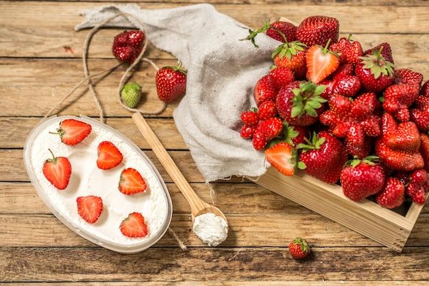 Anordnung mit frischen erdbeeren auf holztisch
