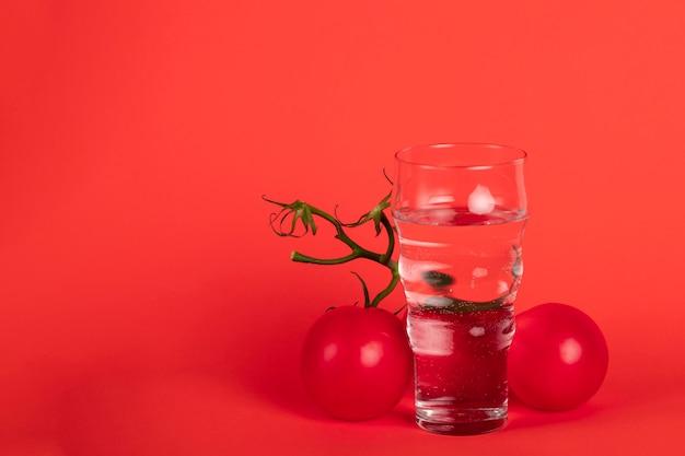 Anordnung mit glas, tomaten und exemplarplatz