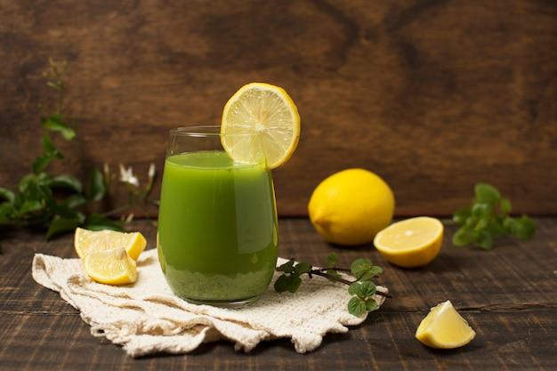 Anordnung mit grünem smoothie und zitronen