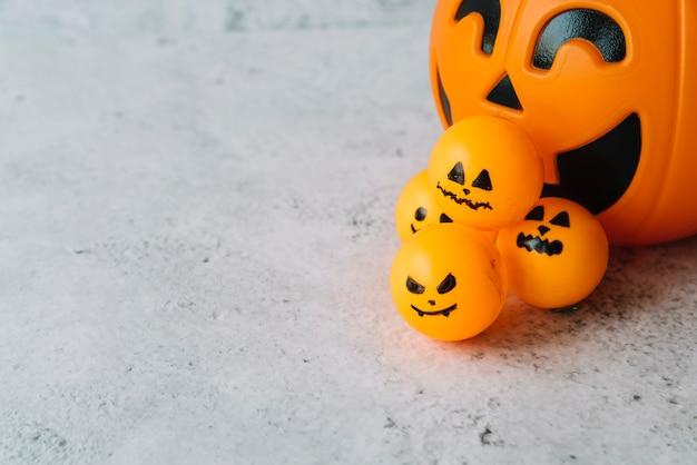 Anordnung mit halloween-korb und kleinem ball mit furchtsamen gesichtern