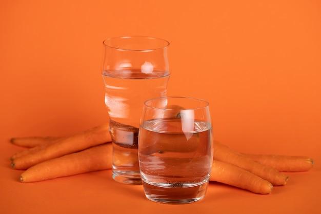Anordnung mit karotten und gläsern wasser