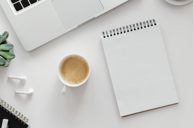 Anordnung mit leerem notizblock auf dem schreibtisch