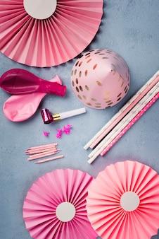 Anordnung mit rosafarbenem partyhut und kerzen