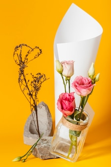Anordnung mit rosen in einer vase mit einem papierkegel