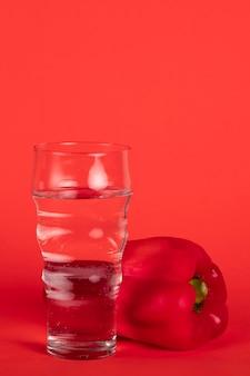 Anordnung mit rotem pfeffer und glas wasser