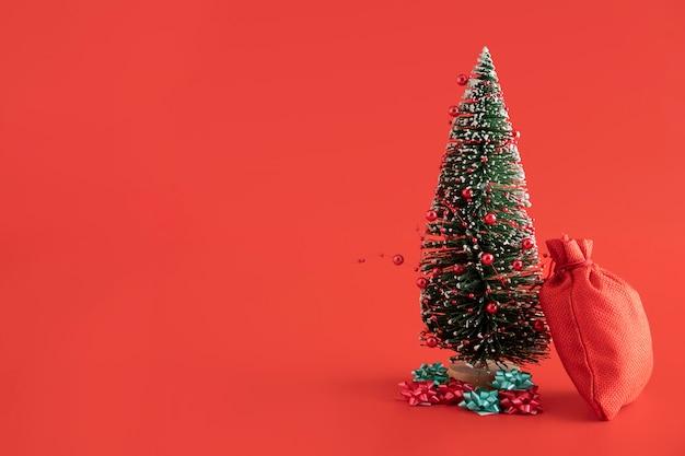 Anordnung mit rotem sack und tannenbaum