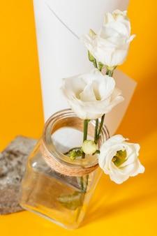 Anordnung mit weißen rosen in einer vase mit einem papierkegel