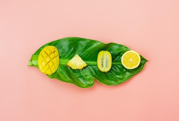 Anordnung schnitt verschiedene kiwimangozitrone und -ananas auf grünen blättern einzelteile auf rosa papier