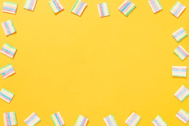 Anordnung verschiedenfarbiger bonbons auf gelbem hintergrund mit kopierraum