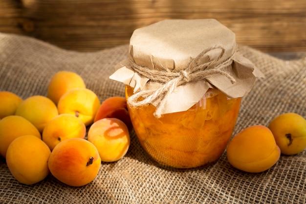 Anordnung von aprikosen auf stoff mit kompottglas
