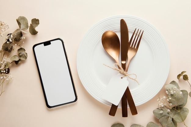 Anordnung von elegantem geschirr mit leerem smartphone