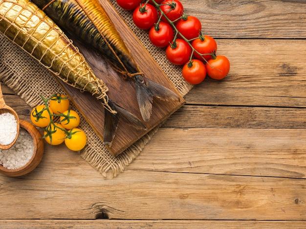 Anordnung von geräucherten fischen und tomaten