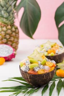 Anordnung von kokosnüssen mit obstsalat gefüllt