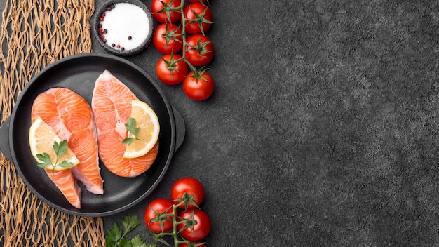 Anordnung von lachsfisch und tomaten mit meeresfrüchten