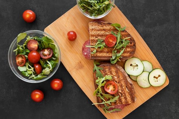 Anordnung von leckeren sandwiches auf holzbrett