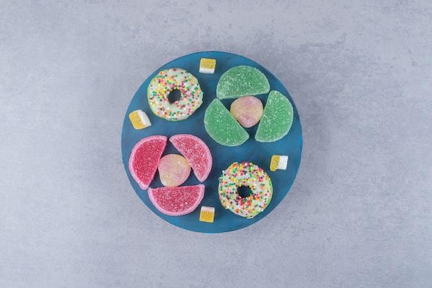 Anordnung von marmeladen und donuts auf einem blauen brett auf marmoroberfläche