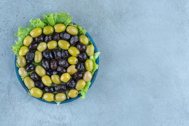 Anordnung von oliven ohne grube auf einer mit salat bedeckten platte auf einem marmortisch.