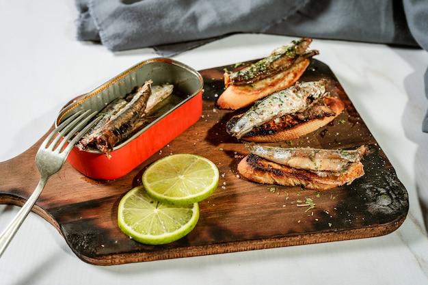 Anordnung von spanischen tapas von sardinen in olivenöl auf toast auf einem rustikalen holzbrett und einer dose sardinen neben den tapas. hohe aussicht.