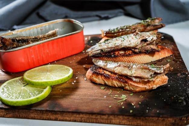 Anordnung von spanischen tapas von sardinen in olivenöl auf toast auf einem rustikalen holzbrett und einer dose sardinen neben den tapas.