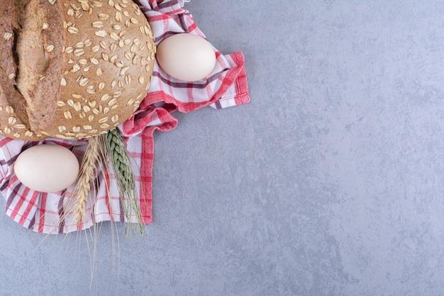 Anordnung von weizenstielen, eiern und einem laib brot auf einem handtuch auf marmoroberfläche