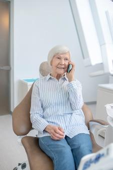 Anruf. ältere frau, die in der zahnarztpraxis sitzt und telefoniert