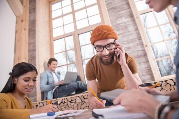 Anruf. positiver netter bärtiger mann, der nahe dem tisch steht und smartphone an sein ohr legt, während er einen anruf tätigt
