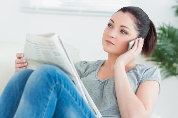 Anrufen der frau, die auf der couch sitzt und die nachrichten liest