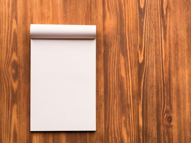 Anschlagtafel mit leerem blatt für anmerkungen im abstrakten leeren hölzernen hintergrund. notizbuch mit em