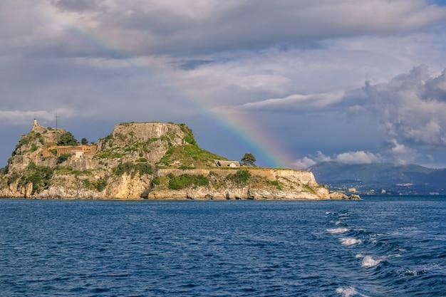 Ansicht der alten venezianischen festung auf dem hügel auf korfu-insel, griechenland. alte steinmauern, bedeckt mit grünem gras, meeresbucht, blauem himmel und regenbogen
