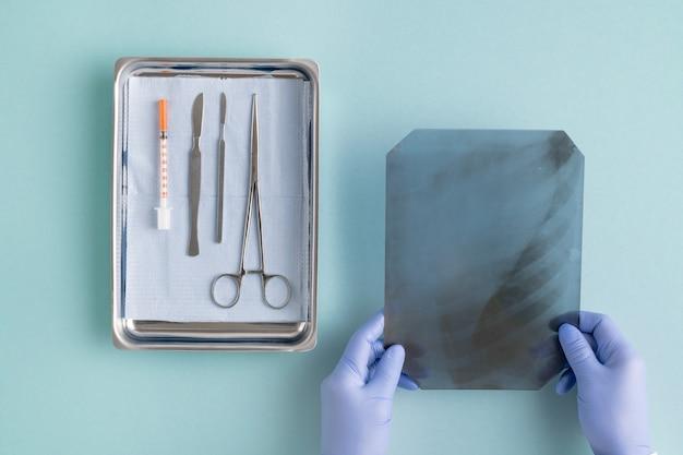 Ansicht der behandschuhten hände des chirurgen, der röntgenbild der lunge am arbeitsplatz mit medizinischen instrumenten und spritze in stahlschale setzt
