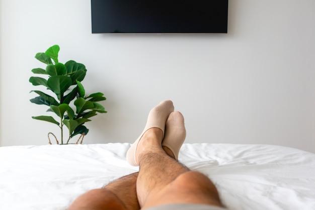 Ansicht der beine des mannes auf weißem bett mit fernseher und pflanze. konzept der entspannung.