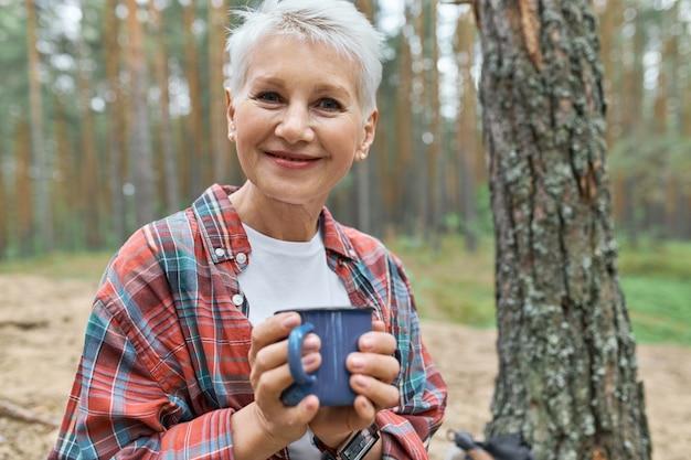 Ansicht der entzückenden glücklichen europäischen rentnerin mit blonden haaren, die sich draußen auf dem campingplatz ausruhen
