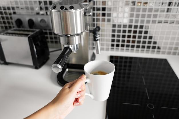 Ansicht der ersten person eines mädchens, das köstlichen aromatischen kaffee in einer kaffeemaschine zubereitet