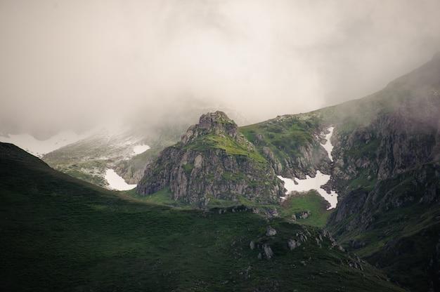 Ansicht der felsigen berge unter dem weißen nebel bedeckt mit gras mit den schneeresten