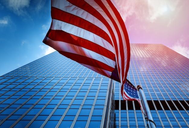 Ansicht der flagge der vereinigten staaten von amerika, die in einen hochhaus-glasturm fliegen