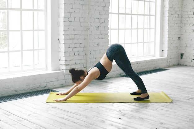 Ansicht der flexiblen jungen frau in voller länge mit schlankem körper, der in der fitnesscenterhalle trainiert, yoga macht, mit matte auf holzboden trainiert, nach unten gerichteten hund oder adho mukha svanasana-pose macht