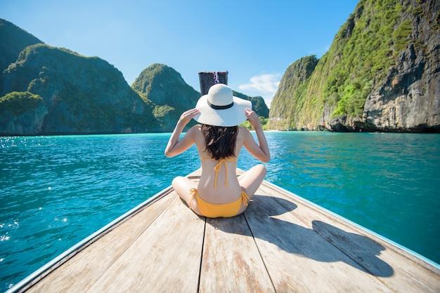Ansicht der frau im badeanzug, die auf thailändischem traditionellem langschwanzboot über schönem berg und ozean, phi phi islands, thailand genießt