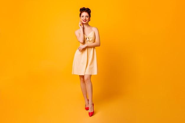 Ansicht der fröhlichen pinup-dame in voller länge. attraktive junge frau im kleid, das auf gelbem raum steht.