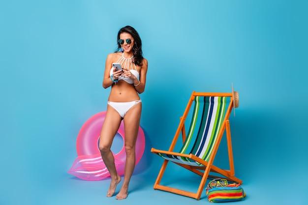 Ansicht der gebräunten frau in voller länge im bikini unter verwendung des smartphones