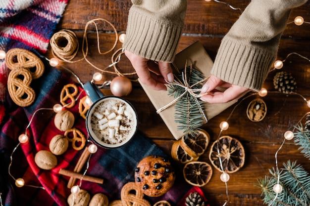 Ansicht der hände der jungen frau, die knoten oben auf geschenkbox unter weihnachtssymbolen, dekorationen und essen macht