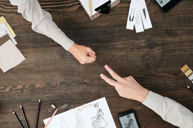 Ansicht der hände von zwei designern, die faust und zwei gestreckte finger zeigen, während sie über saisonale modekollektion durch holztisch arbeiten