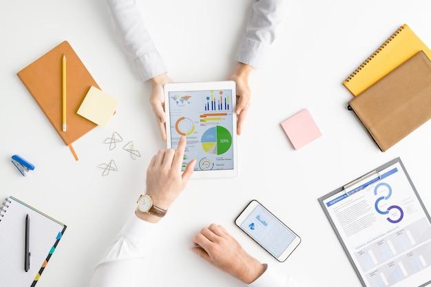 Ansicht der hände zweier zeitgenössischer analysten oder makler, die finanzdaten auf dem touchscreen diskutieren