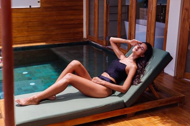 Ansicht der hübschen gebräunten perfekten hautfrau aus bronze im alten vintage-bikini der schwarzen weinlese liegt auf grünem sonnenbett in erstaunlicher villa am sonnigen tag, ruhend, genießt urlaub.