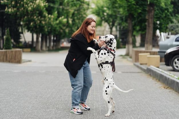 Ansicht der jungen kaukasischen frau, die ihren dalmatinerhund spielt und trainiert