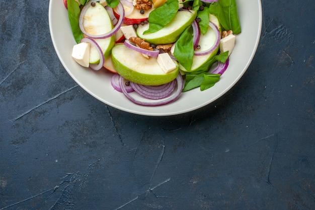 Ansicht der oberen hälfte des frischen apfelsalats in der schüssel auf dunkelblauem hintergrund