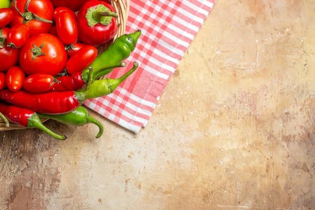 Ansicht der oberen hälfte grüne und rote paprikaschoten, tomaten in weidenkorb und küchentuch auf bernsteinfarbenem hintergrund
