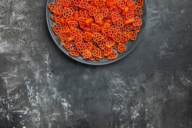 Ansicht der oberen hälfte herzförmige italienische pasta auf schwarzer ovaler platte