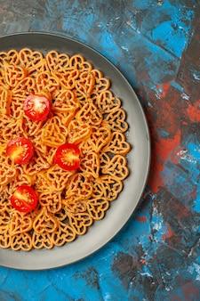 Ansicht der oberen hälfte italienische pasta herzen schneiden kirschtomaten auf schwarzem ovalen teller